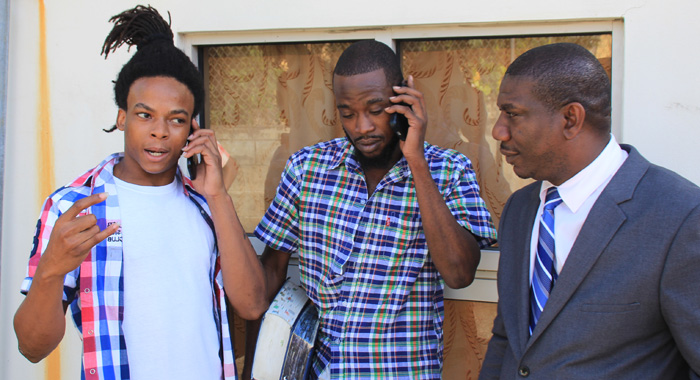 Kemroy Craigg, left, and Derrol Small speak with persons via cellphone after the court hearing while lawyer Israel Bruce looks on. (IWN photo)