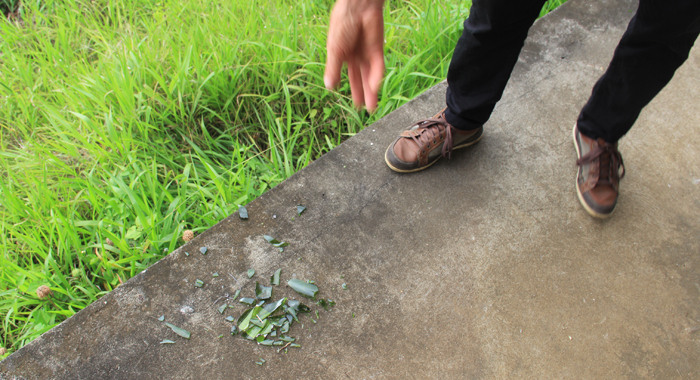 Corea points out broken glass from a bottle of wine that reportedly fell from the intruders and broke Friday night. (IWN photo)