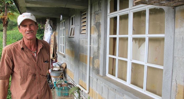 Corea stands next to a broken window through which intruders removed a 160-lbs safe on May 6. (IWN photo)
