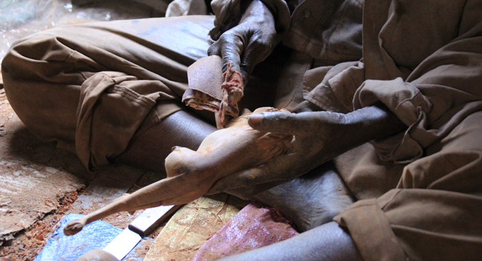 A man sands a wooden carving outside a craft shop in Dakar. (IWN photo)
