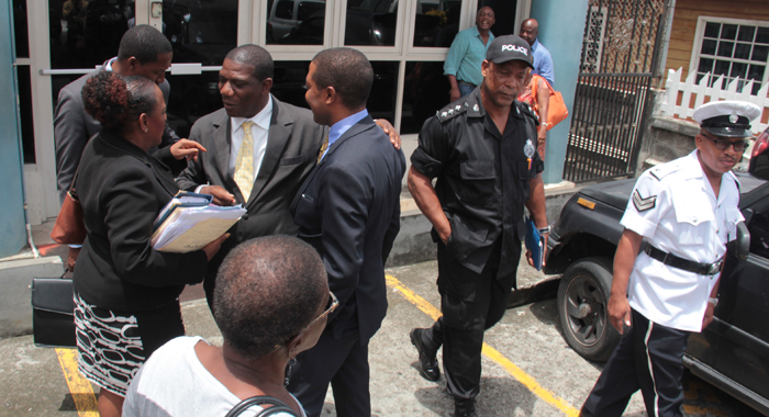 Monday's hearing was initially expected to see the defence cross-examining Assistant Superintendent of Police Timothy Hazelwood, who is seen here (in black uniform) leaving the court as Exeter and his lawyers speak outside the courthouse on Monday. (IWN photo)