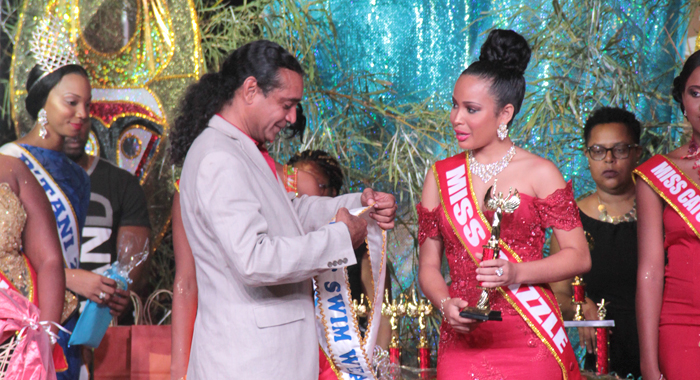 Chair of the P'tani Carnival Committee, Ronnie Marks, left, prepares to sash Best Swimwear winner, Regisha Hazell, who also won the pageant. (IWN photo)