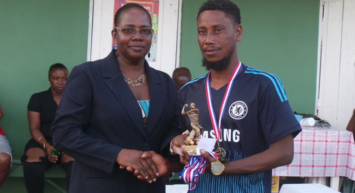Leading wicket-taker, Shanley Lavia collecting trophy from President of Clinchers, Pearlina Thomas.