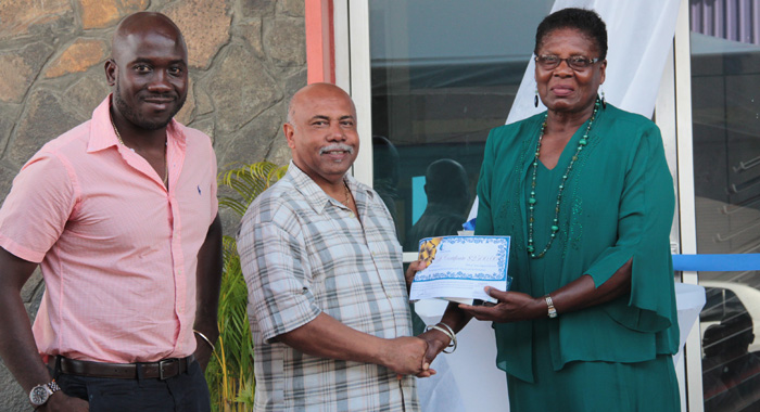 "Sports Minister Cecil ""Ces"" McKie, centre, presents the award to honouree Genita Lewis, right, as Kevin Dickson, chair of Coreas Pharmacy Council looks on. (IWN photo)"