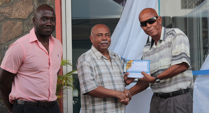 "Sports Minister Cecil ""Ces"" McKie, centre, presents the award to honouree Stanley ""Gunny"" Hinds, right, as Kevin Dickson, chair of Coreas Pharmacy Council looks on. (IWN photo)"