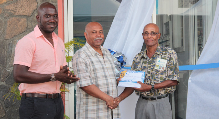 "Sports Minister Cecil ""Ces"" McKie, centre, presents the award to honouree Guy Lowe, right, as Kevin Dickson, chair of Coreas Pharmacy Council looks on. (IWN photo)"