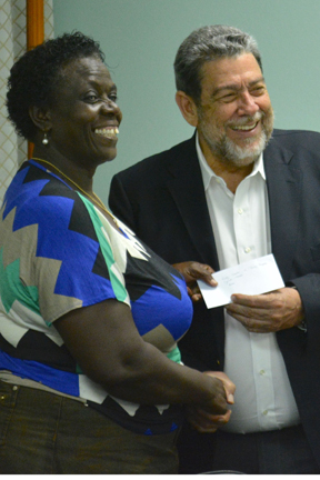 A parent receives a cash grant from PM Gonsalves. (Photo: API)