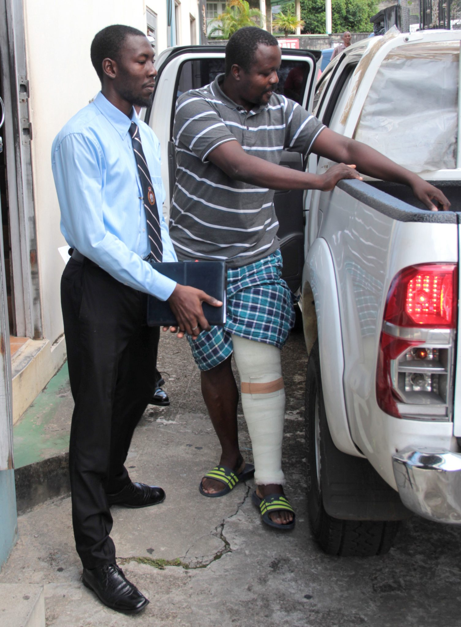 Accused robber, Kimolow Quashie, right, reaches for his crutches as he arrives at the court building on Tuesday. (IWN photo)