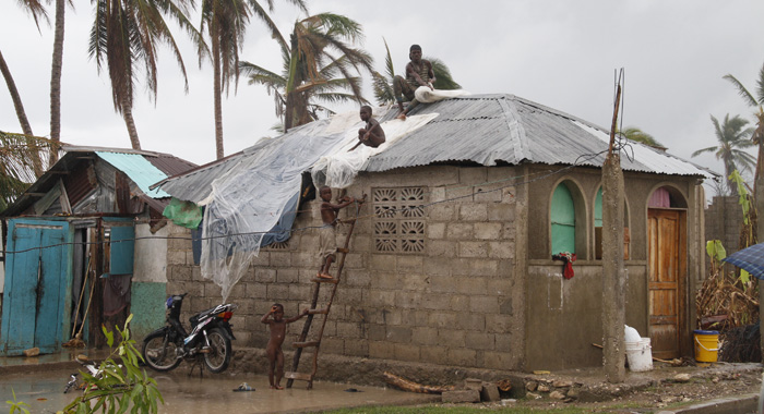A Group Of Boys Makes A Desperate Attempt On Monday To Patch The Roof Of A House In Les Cayes Damaged By Hurricane Matthews