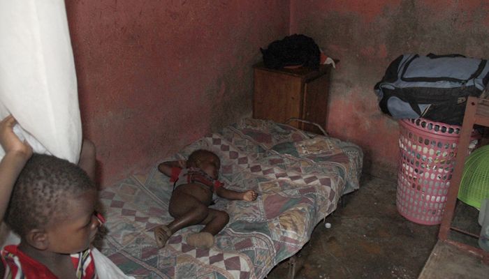 A 2-year-old infant sleeps in a small room in Haiti, where she lives with her mother and three siblings. (CMC photo)