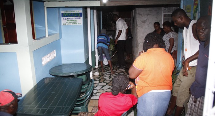 Some of Reid's relatives wash away blood from the murder scene Wednesday night. (IWN photo)