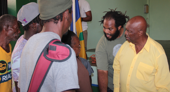Arnhim Eustace, in yellow, and his son Ajene Eustace, with dreadlocks, interact with persons after an NDP press conference last December. (IWN photo)