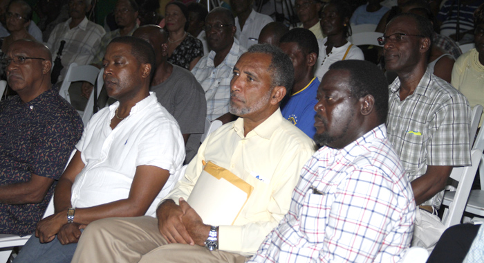 Leader of the Opposition and NDP vice-president, Godwin Friday, with binder, and MP for the Southern Grenadines, Terrance Ollivierre, to Friday's left, listen to Eustace speak Tuesday night. (IWN photo)