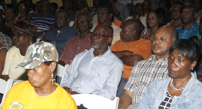 Leacock, in blue shirt, and NDP chairman, Dr. Linton Lewis, to his left, and other persons listen to Eustace's speech Tuesday night. (IWN photo)