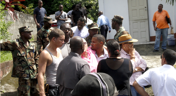 Patrick McIntosh, in pink, attempt to prevent police from removing the bodies. (IWN photo)