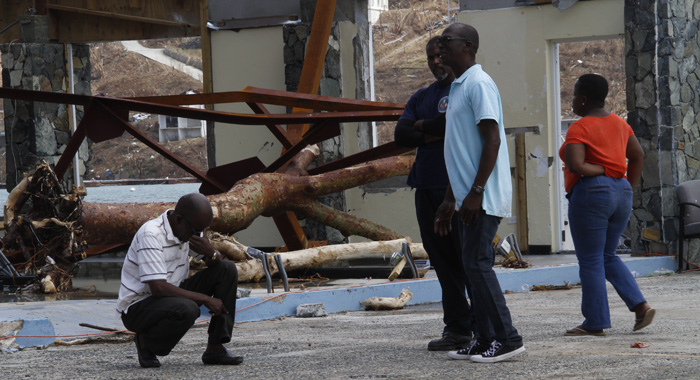 Commissioner Of Customs Aubrey Forbes Stoops After Surveying The Damage At The Jost Van Dyke Ferry Terminal In West End Tortola. Cmc Photo.jpg